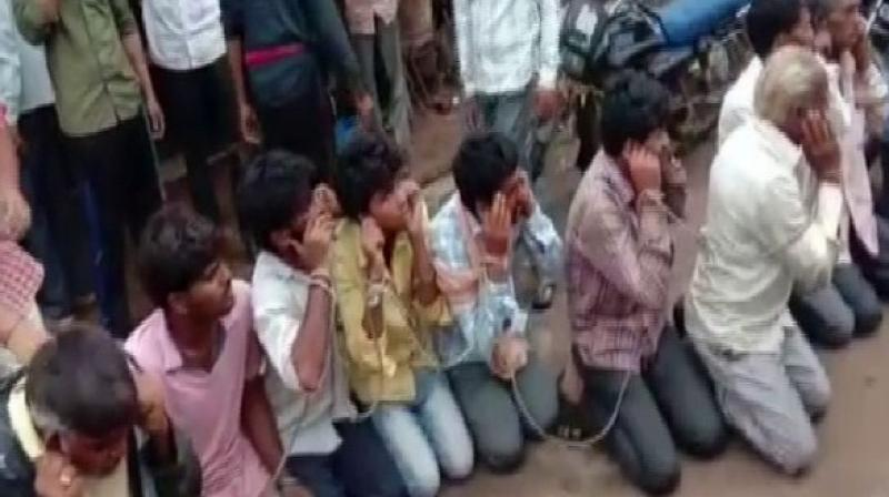 In a video which has gone viral, they were tied to a rope in public, made to kneel down and forced to chant