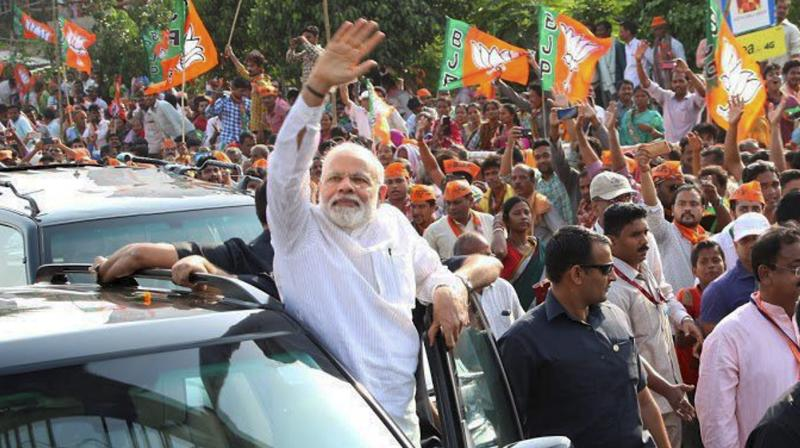 Prime Minister Narendra Modi acknowledges his supporters during a roadshow in Bhubaneswar. (Photo: PTI)
