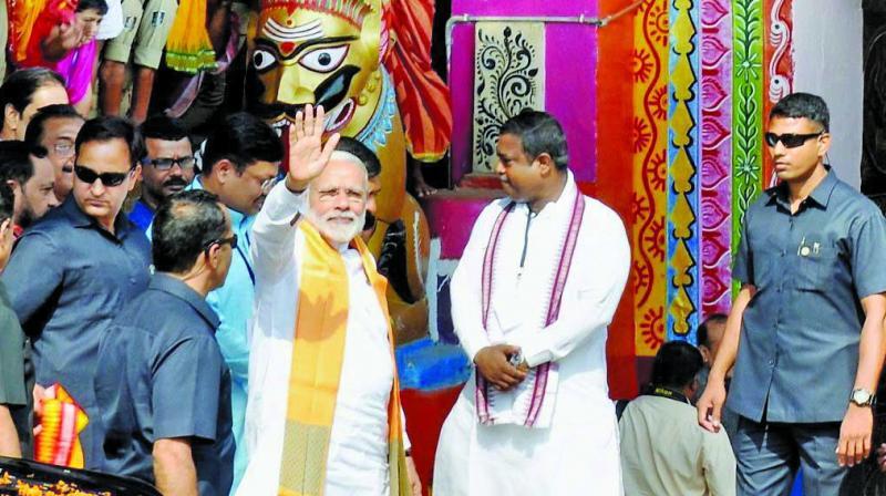 Prime Minister Narendra Modi waves to people at the Lord Lingaraj temple in Bhubaneshwar. (Photo: PTI)