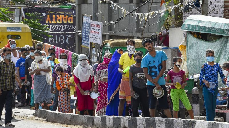 People stand in a queue to collect food, distributed by volunteers during the ongoing nationwide lockdown in the wake of coronavirus pandemic, in East Delhi. PTI photo