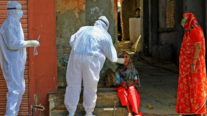 A medic collects a swab sample of an elderly woman during a door-to-door examination of COVID-19 amid a nationwide lockdown imposed in the wake of coronavirus pandemic in Jaipur. PTI photo