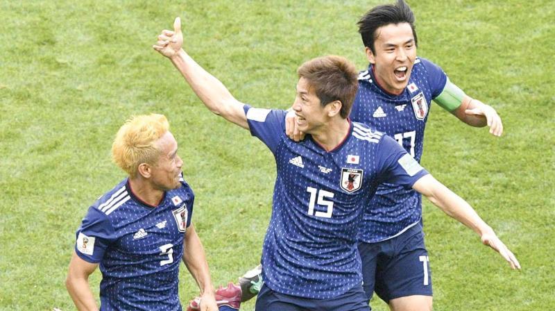 Japanese striker Yuya Osako (centre) celebrates with Yuto Nagatomo (left) and Makoto Hasebe after scoring against Colombia in Saransk on Tuesday. (Photo: AFP)