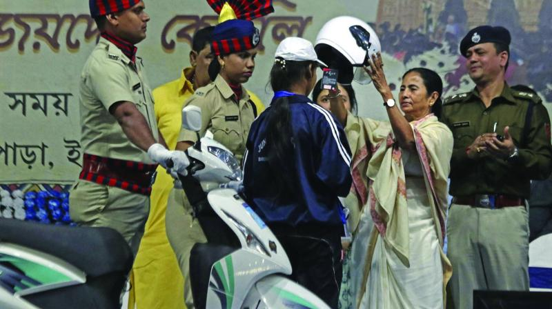 CM Mamata Banerjee presents a helmet during a development programme in Birbhum on Thursday. (Photo: PTI)