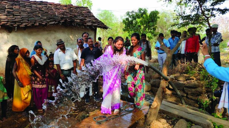 Priyadarshini Raje Scindia drinks water from a  tubewell at a village.