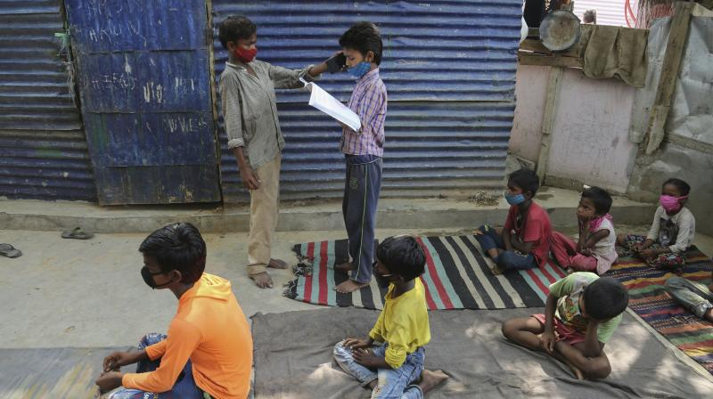 A student holds a mobile phone for another so that he can listen to instructions from a teacher as children wearing face masks as a precaution against the coronavirus attend online classes at a slum on the outskirts of Jammu. (Photo: PTI)