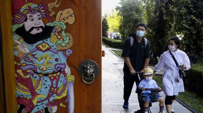 Residents wearing masks to curb the spread of the coronavirus walk on a Beijing street. (AP)