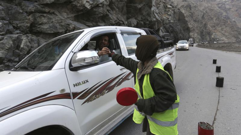 11-year-old Sedaqat receives a tip from a motorist on the Maipur Pass, along the main highway from Kabul to Pakistan, near Kabul, Afghanistan. (Photo: AP)