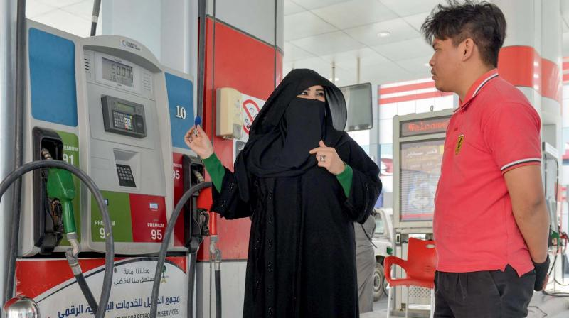 Saudi gas station supervisor Mervat Bukhari (right) talks to a worker at her workplace in Khobar, 400 km east of Riyadh. (Photo: AFP)