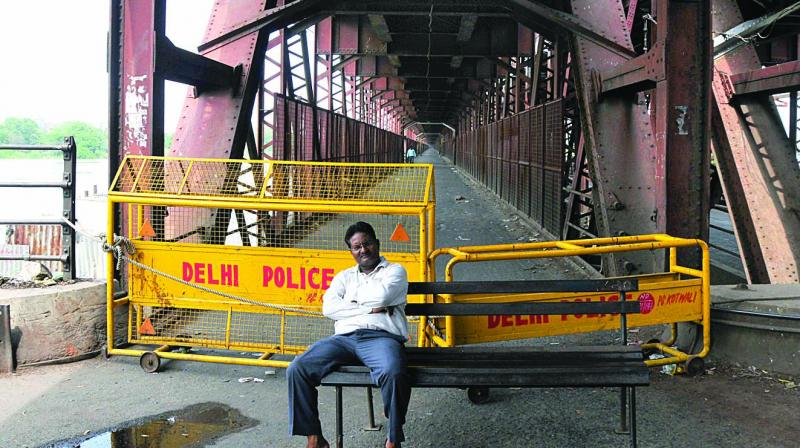 A man sits near police barricades at the Old Yamuna Bridge near Red Fort on Monday. The bridge has been shut after Yamuna crossed the danger mark.  (Photo: Bunny Smith)