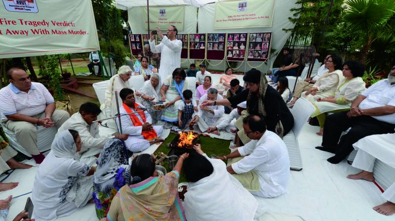 Family members and relatives of victims of the Uphaar fire tragedy take part in special prayers near the cinema hall at Green Park, New Delhi, on Tuesday, the 20th anniversary of the incident. (Photo: Asian Age)