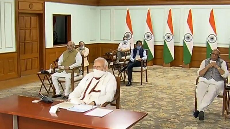 Prime Minister Narendra Modi wearing a protective mask chairs a meeting with chief ministers on COVID-19 lockdown via video conference, in New Delhi, Saturday, April 11, 2020. Union Home Minister Amit Shah, Defence Minister Rajnath Singh and others are also seen. (Photo | PTI)