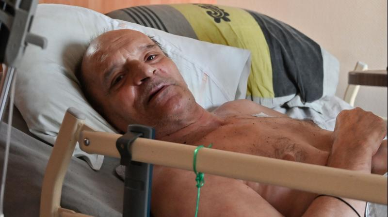 Alain Cocq, suffering from an orphan desease of the blood, rests on his medical bed in his flat in Dijon, northeastern France. (AFP)