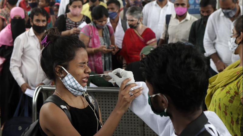 A health worker collects a swab sample from a traveler to test for COVID-19 at a train station in Mumbai. (Photo: AP)_