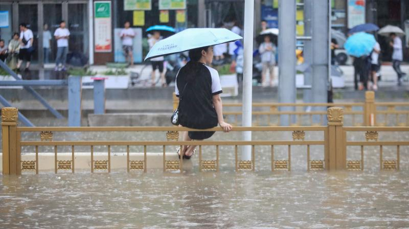 A woman sitting on a fence on a flooded street following heavy rains in Zhengzhou in China's central Henan province. (Photo: AFP)