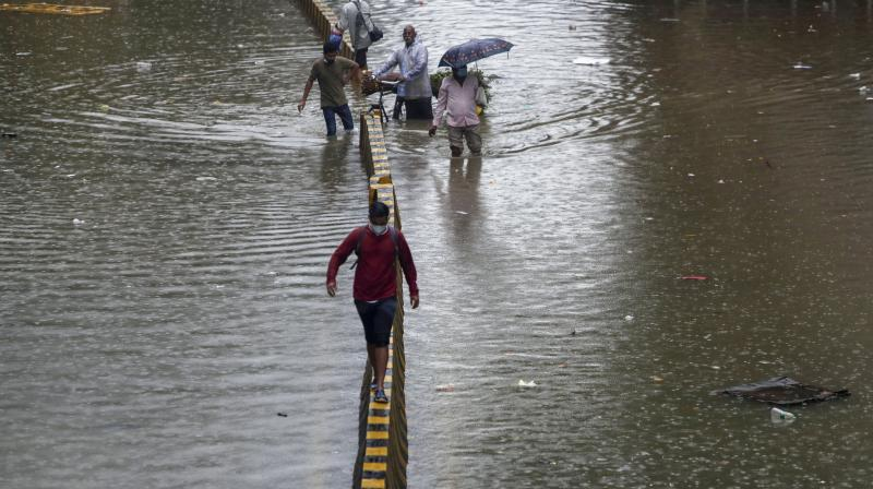 People make their way through a waterlogged street after heavy rainfall in Mumbai. (Photo: PTI)
