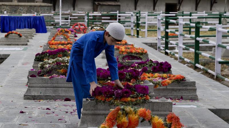A Kashmiri boy lays a wreath on a grave at Martyr's Graveyard in Srinagar, Kashmir on Saturday. (Photo: AP)