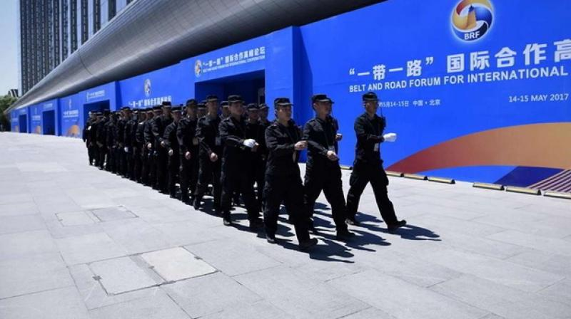 A group of security guards walk past a billboard for the Belt and Road Forum for International Cooperation. (AFP)