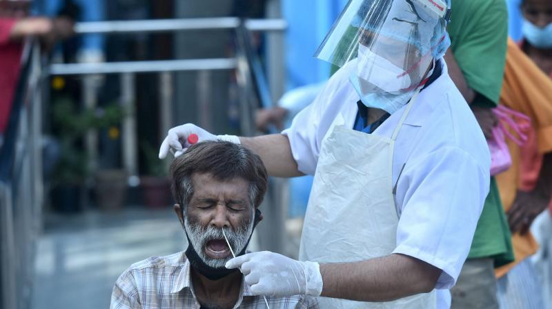 A health worker collects swab sample from a person for COVID-19 test, near Kashmere Gate in New Delhi. (PTI)