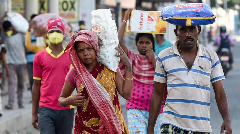 Migrant workers carry sacks of groceries distributed at their workplace during coronavirus lockdown (PTI)