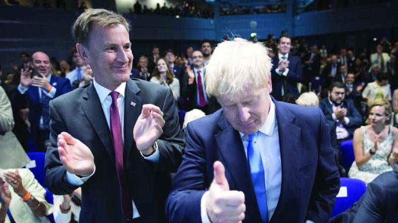 Jeremy Hunt (left) congratulates Boris Johnson after the announcement of the result in the ballot for the new Conservative party leader in London on Tuesday. Brexit hardliner Johnson won the contest to lead Britain's governing Conservative Party on Tuesday and will become the country's next Prime Minister. (Photo: AP)