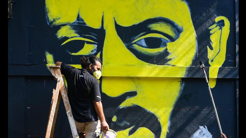An artist paints a mural of Bollywood actor Irrfan Khan on a wall, in Mumbai. PTI Photo