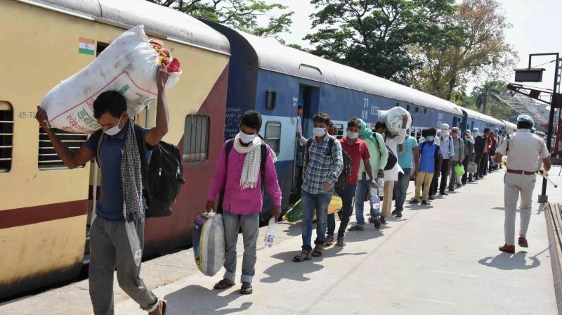 Patna: A health worker sanitizes migrants who have arrived from Jaipur by 'Shramik Special' train at Danapur junction, during the nationwide lockdown to curb the spread of coronavirus, in Patna. PTI Photo