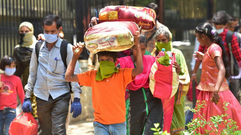 Migrants carrying their luggage arrive at the District Collector's office for arrangements to return to their native places, amid ongoing COVID-19 lockdown in Bengaluru. PTI Photo