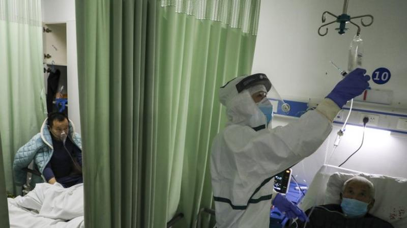 A nurse checks on a patient in the isolation ward for 2019-nCoV patients at a hospital in Wuhan in central China's Hubei province. The number of confirmed cases of the new virus has risen again in China. AP photo