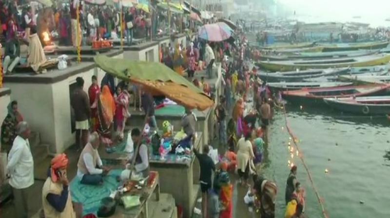 Devotees take a holy dip in River Ganga in Varanasi on Sunday. ANI photo