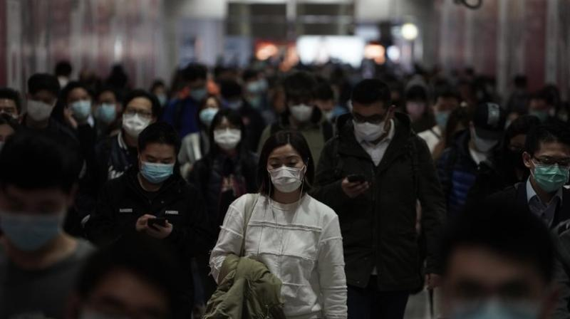 People wearing masks, walk in a subway station, in Hong Kong. AP photo