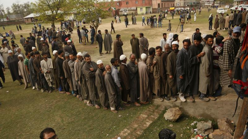 Kashmiri voters stand in a queue to cast their votes outside a polling station at Shadipora. (Photo: AP)