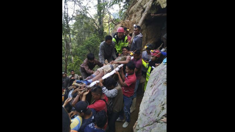 Indonesian officials said on Wednesday dozens of rescuers were using spades and ropes to dig out more than 60 people. (Photo:AP)