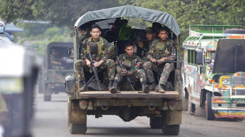 Soldiers ride a military vehicle on the outskirts of Marawi city, southern Philippines. The Philippine military says 13 marines have been killed in fierce fighting with Muslim militants who have laid siege to southern Marawi city. (Photo: AP)
