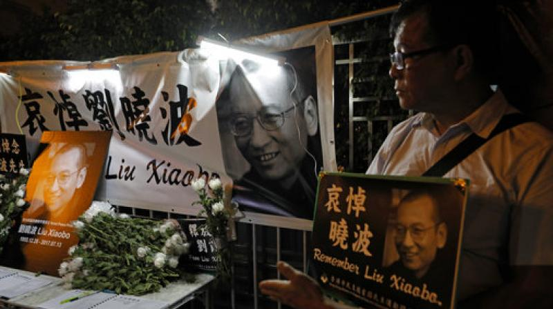 Protesters mourn jailed Chinese Nobel Peace laureate Liu Xiaobo during a demonstration outside the Chinese liaison office in Hong Kong. (Photo: AP)