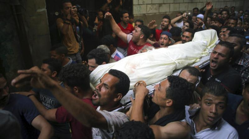 People carry the body of Sayed Tafshan, who died during clashes between security forces and residents of al-Waraq island, on the northern fringes of Cairo, Egypt. (Photo: AP)