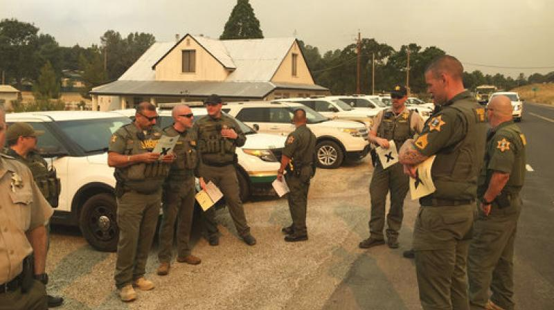 Merced and Mariposa County Sheriff's Office members attend a briefing during a wildfire in Mariposa County, California. (Photo: AP)