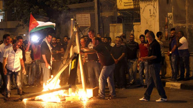 Palestinians burn mock metal detectors during a demonstration in Bethlehem. Israel's minister of public security said Sunday that metal detectors set at the entrance to a major Jerusalem shrine that angered Palestinians could be removed if police have another way of ensuring security there. (Photo: AP)