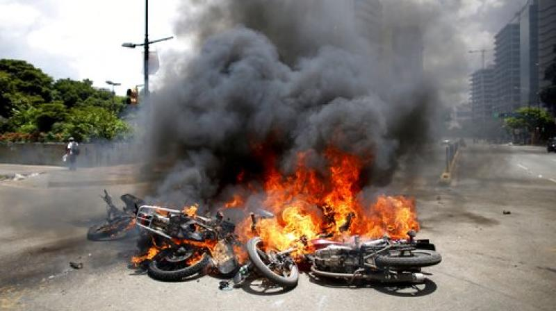 Venezuelan Bolivarian National police move away from the flames after an explosion at Altamira square during clashes against anti-government demonstrators in Caracas, Venezuela. The explosion injured several officers and damaged several of their motorcycles. The officers were then seen throwing several privately owned motorcycles into the remaining fire in reprisal. (Photo: AP)