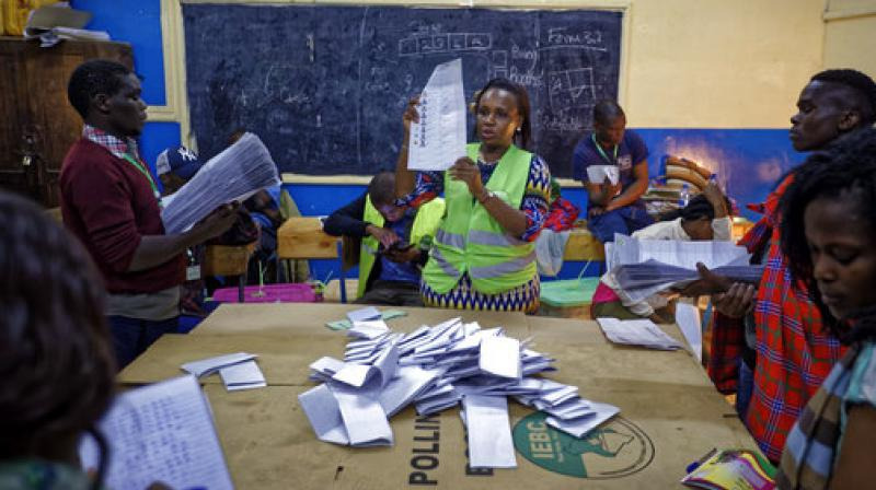 An electoral counting officer, center, counts votes while others hold the piles of ballots counted for each candidate, at a polling station in Nairobi, Kenya. (Photo: AP)