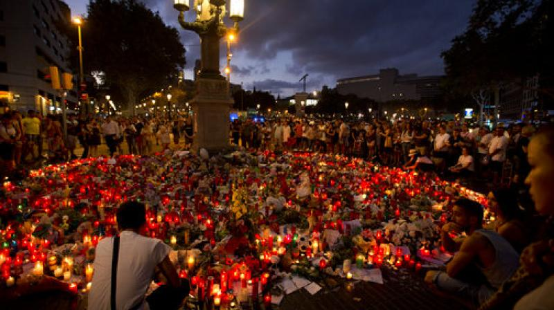 People stand next to candles and flowers placed on the ground, after a terror attack that killed at least 14 people and wounded over 120 in Barcelona, Spain. (Photo: AP)