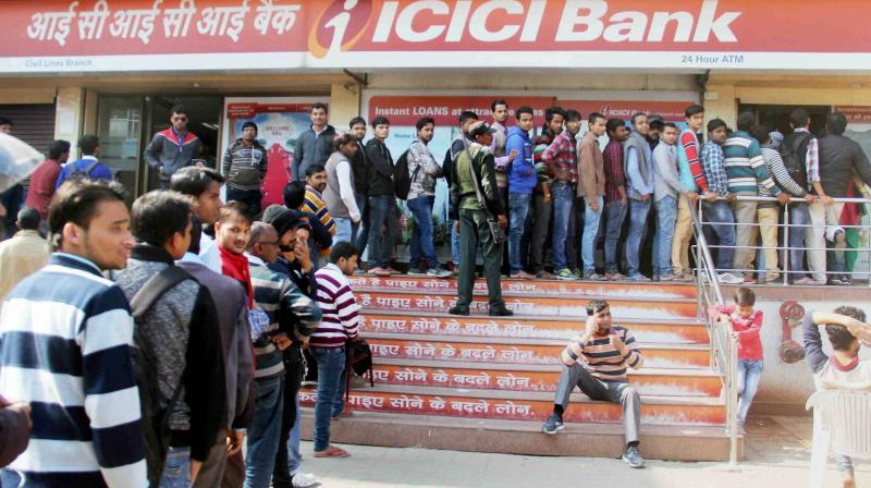 People stand in long queues outside an ATM at a bank to withdraw cash after the ban on old high denomination notes. (Photo: PTI)