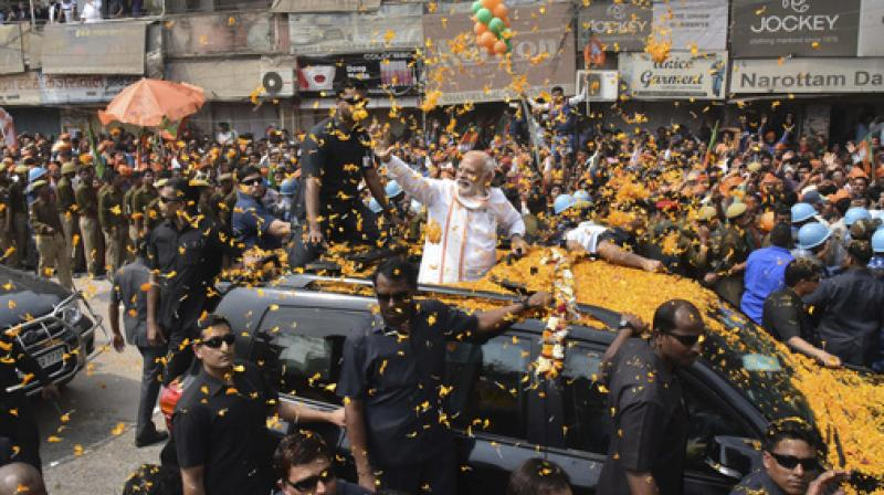 Prime Minister Narendra Modi waves to supporters as he campaigns for his party in the Uttar Pradesh state elections in Varanasi. (Photo: AP)