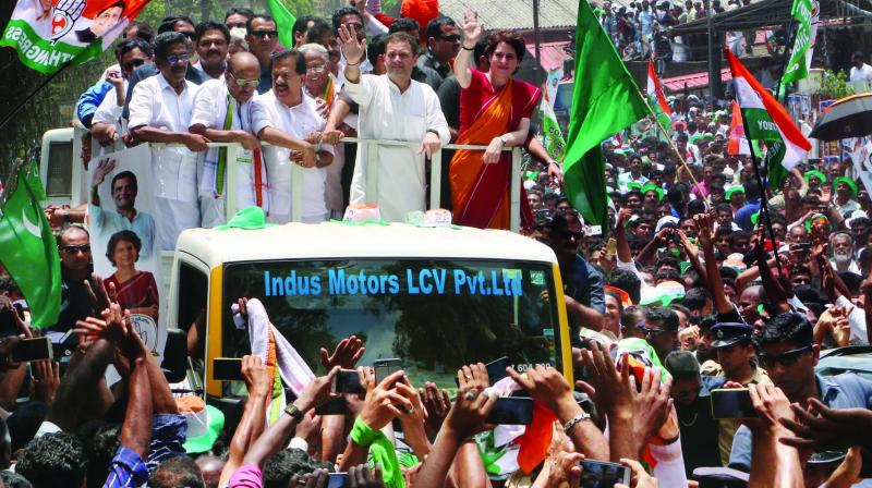 Congress president Rahul Gandhi, with party general secretary Priyanka Gandhi Vadra and other leaders, waves at party supporters during a roadshow after filing his nomination papers for the Wayanad seat on Thursday.