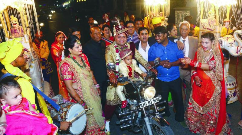 A bridegroom rides a bike in his marriage procession due to a ban on use of mares.