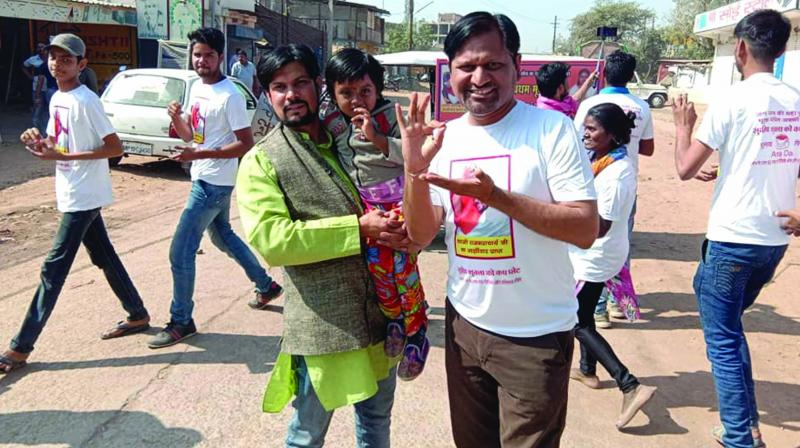 Sudeep Shukla carries a child during campaigning