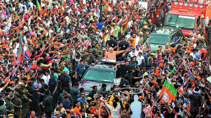 Prime Minister Narendra Modi waves at supporters during his roadshow a day ahead of filing his nomination papers for the Lok Sabha polls in Varanasi on Thursday. (Photo: PTI)