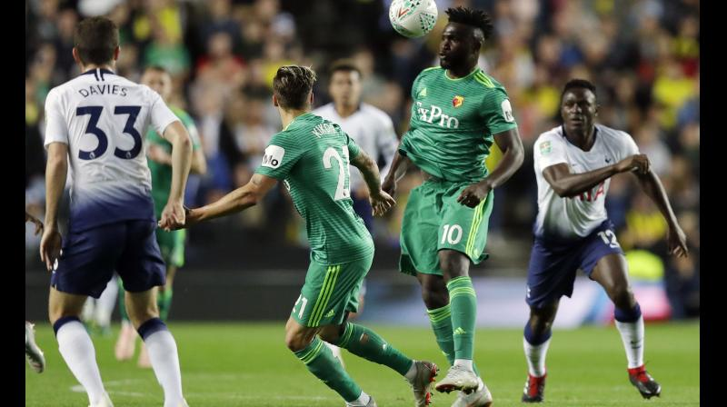 Watford's Isaac Success (C) challenges for the ball with Tottenham's Victor Wanyama (R) during the English League Cup soccer match. AP Photo