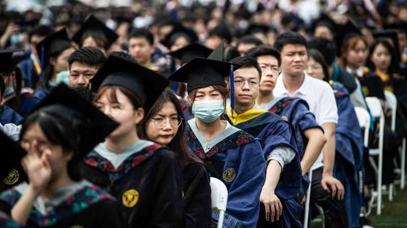 This photo taken on June 13, 2021 shows nearly 9000 graduates, including more than 2000 students who could not attand the graduation ceremony last year due to the Covid-19 coronavirus outbreak, attanding a graduation ceremony at Central China Normal University in Wuhan, in China's central Hubei province. (Photo by STR / AFP) / China OUT
