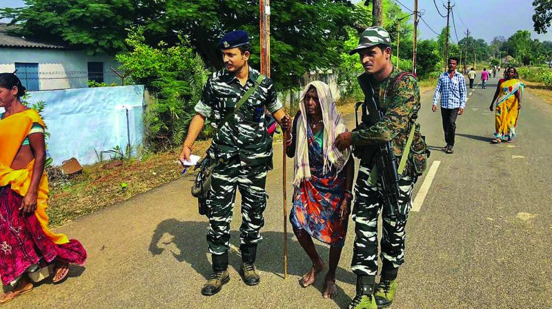 CRPF personnel help an elderly voter to reach a polling station in Sukma district. (Photo: PTI)