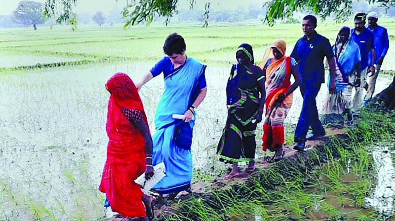 Congress leader Priyanka Gandhi Vadra with locals in Sonbhadra district's Ubha village Tuesday. (Photo: PTI)